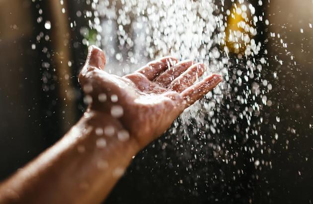 main sous l'eau chaude de la douche