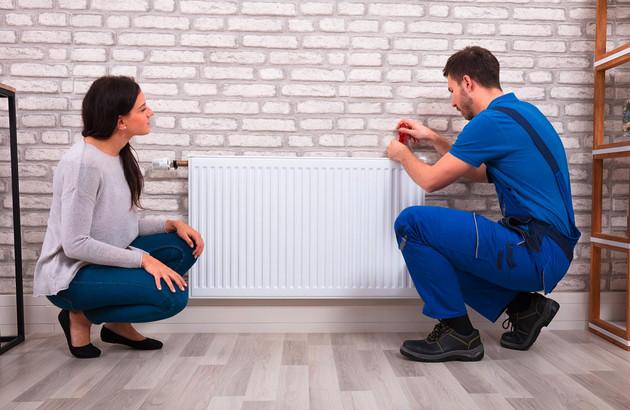 chauffagiste vérifiant le radiateur d'une cliente