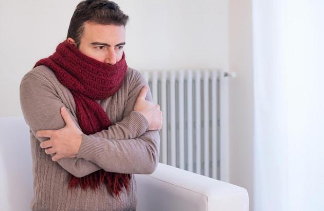 Homme avec écharpe devant radiateur en panne