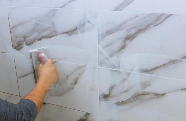 Artisan qui pose du carrelage marbre blanc sur du carrelage