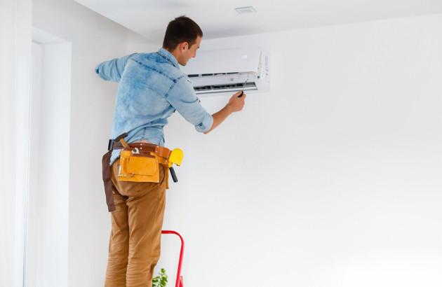 un artisan entrain d'installer une climatisation dans une maison