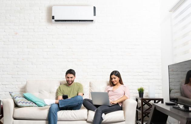 Un jeune couple profitant confortablement de leur climatisation installée par un professionnel