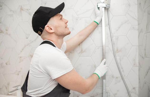 un professionnel installant une douche dans une salle de bains carrelée marbre blanc