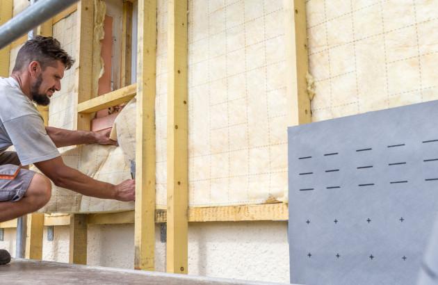 Artisan professionnel effectuant des travaux de rénovation énergétique: isolation des murs extérieurs