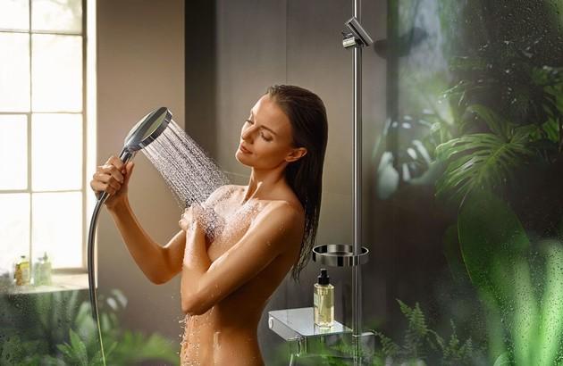 Femme se douchant avec la douchette Powder Rain dans une salle de bains verte