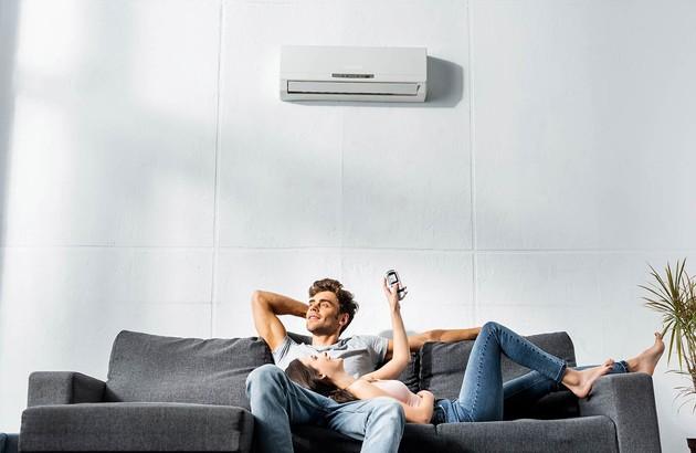 couple de personne placés sous une unité de climatisation murale