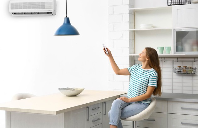 femme assise sur une chaise réglant son unité de climatisation