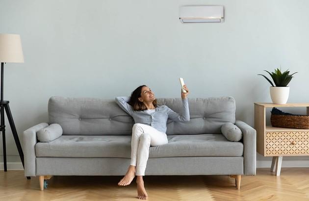 femme sur un canapé utilisant sa télécommande pour régler la climatisation