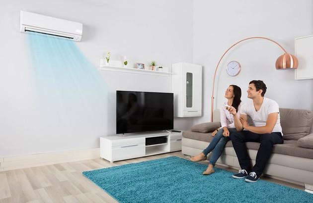 Un jeune couple qui utilise son système de climatisation split gainable