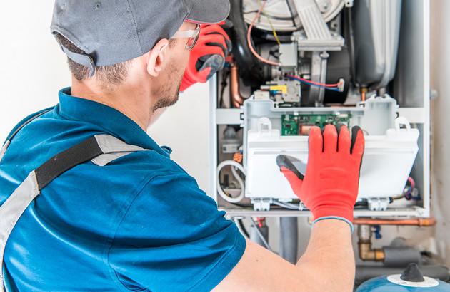 Artisan travaillant sur un radiateur à gaz