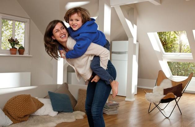 Mère et enfant heureux devant la chaudière gaz écoCompact Vaillant