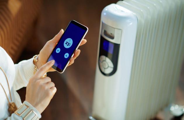 Femme contrôlant son radiateur depuis un smartphone