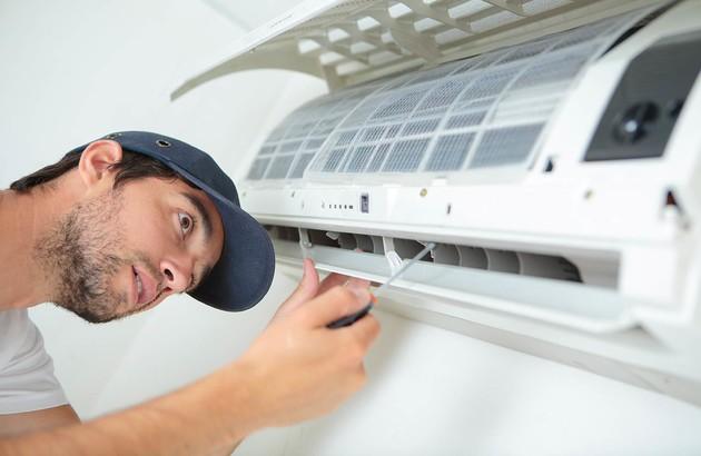 personne qui effectue des ajustements avec un tournevis sur l'appareil de climatisation