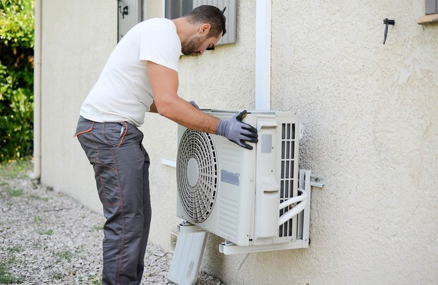 professionnel qui installe le module extérieur de la climatisation