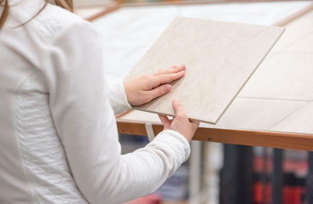 Un femme touche un carreau de carrelage