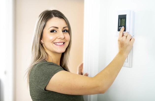 Jeune femme qui utilise un thermostat pour régler sa climatisation