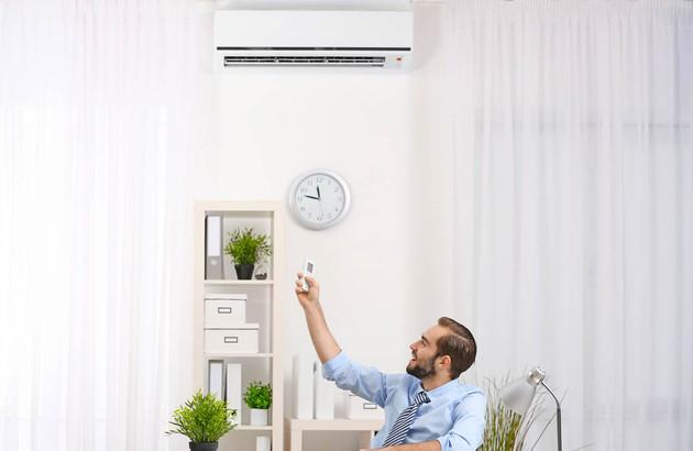 Jeune homme qui utilise une télécommande pour régler son climatiseur