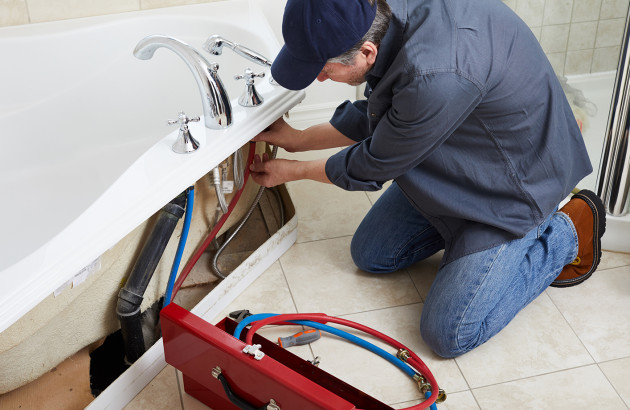 artisan qui répare une baignoire