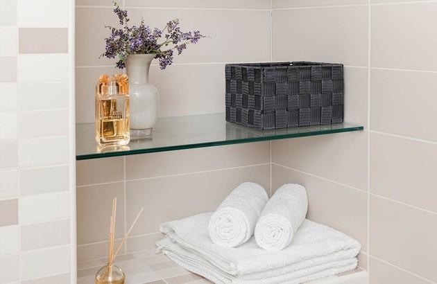 Etagères en verre encastrées dans une niche du mur de salle de bains