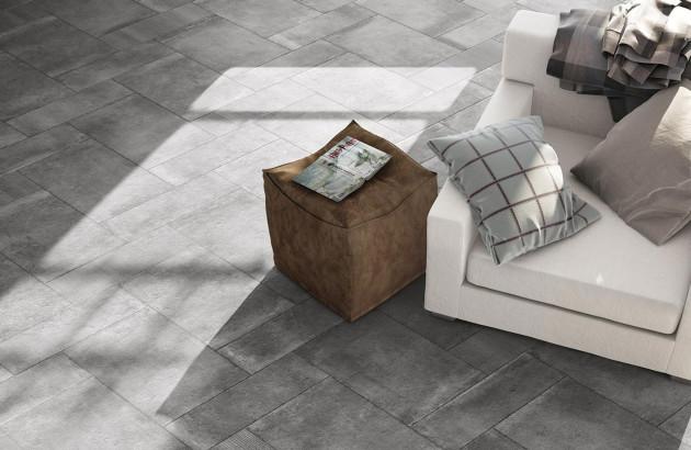 Fauteuil cosy dans salon avec carrelage imitation pierre gris