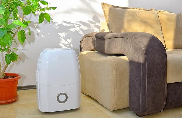 climatiseur mobile à côté d'un canapé