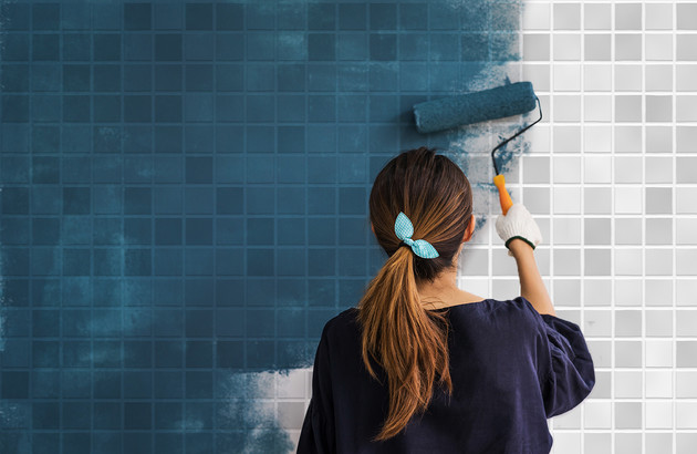 Femme qui peint du carrelage mural