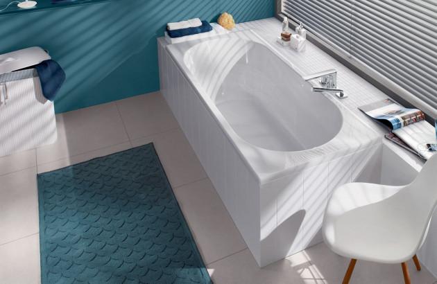 Tuyauterie cachée dans le tablier d'une baignoire d'angle blanche