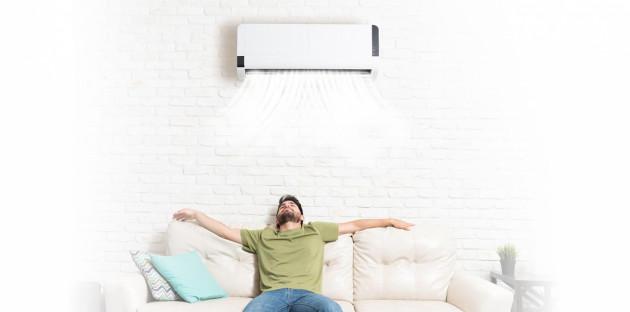 Un jeune homme profitant confortablement de l'installation de sa climatisation par un profesionnel