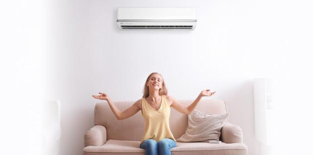 Jeune femme profitant de sa climatisation depuis son canapé