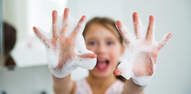 Jeune fille qui profite d'une robinetterie sans contact pour se laver les mains