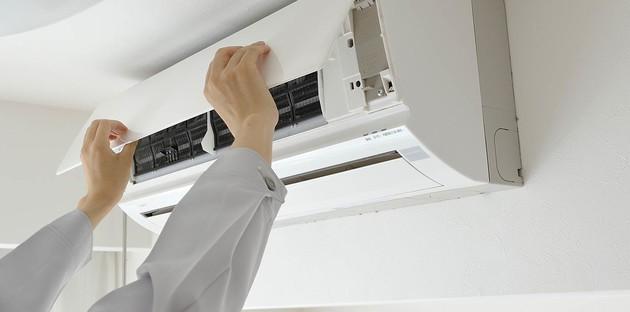 personne réglant son appareil de climatisation