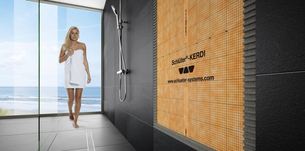Jeune femme en serviette de bain devant douche à l'italienne