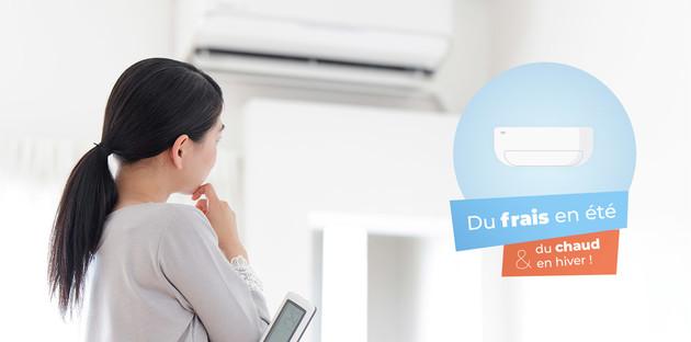 femme regardant son unité de clim murale avec une télécommande