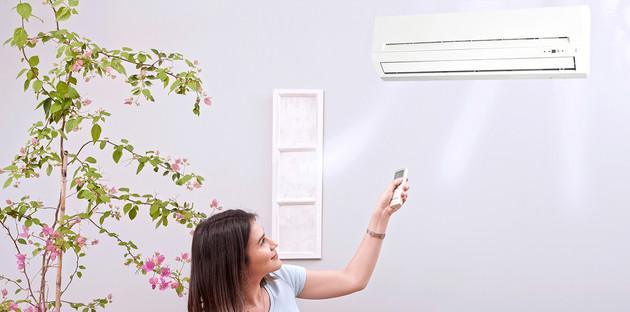 Une femme allumant sa climatisation monosplit