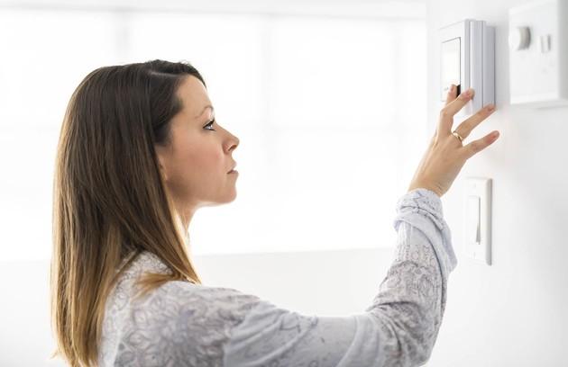 jeune femme qui utilise un thermostat