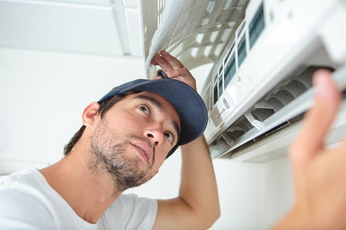 professionnel effectuant l'entretien de la climatisation
