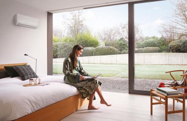 Femme assis dans un lit près d'un climatiseur monosplit Espace Aubade