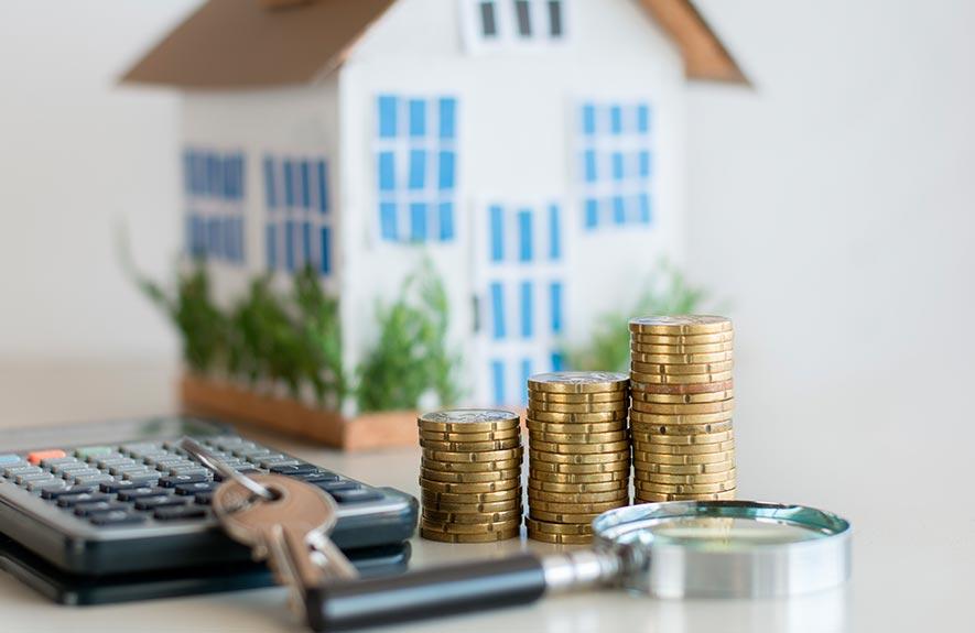 Calculette avec maison et pièces de monnaie